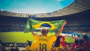 A man holding a Brazilian flag at a soccer game. Portuguese is one of the most spoken language in the world, and you can learn Portuguese online!