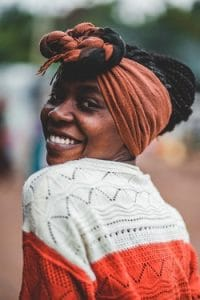 A Kenyan woman smiling. Kenyans speak Swahili, like a lot of Eastern African countries. You can learn Swahili online today.