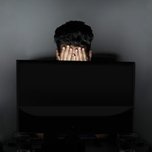 A man sitting in the dark in front of his lit computer screen. Many online ESL students are in different countries than their teachers, so it's important to adjust to the time difference!