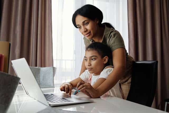 A child sits at the computer and her mother helps her during an Outschool class.