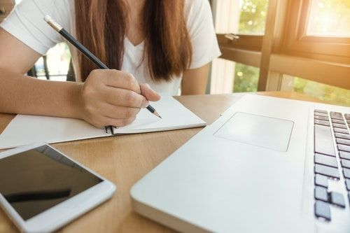 A girl sitting at a desk with her laptop and notebook. She is studying for her online TEFL certificate.