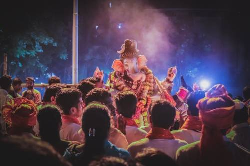 An Indian celebration with an elephant masks and people dancing around and throwing colored powders. When you learn Hindi online, you will learn about Indian culture.