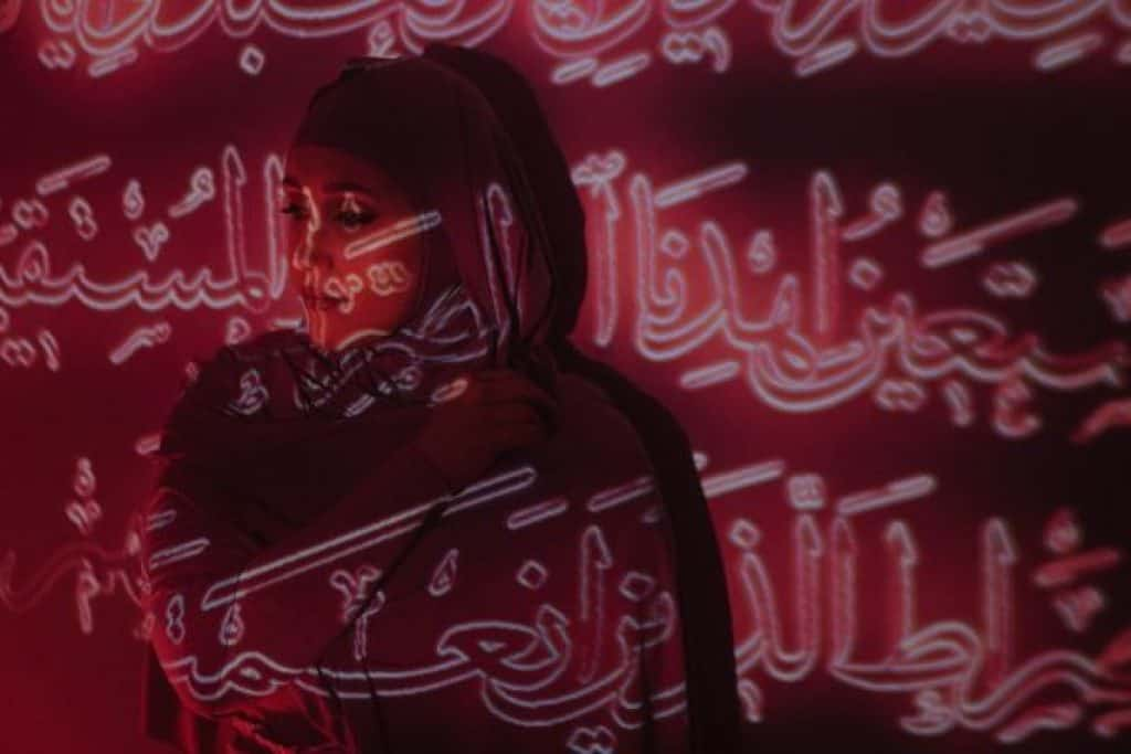 A woman standing against a wall with Arabic text projected over her.