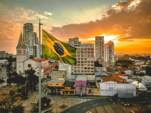A beautiful view of Brazil with the Brazilian flag at the forefront. If you learn Portuguese online, you'll be able to unlock the mysteries of Brazil.